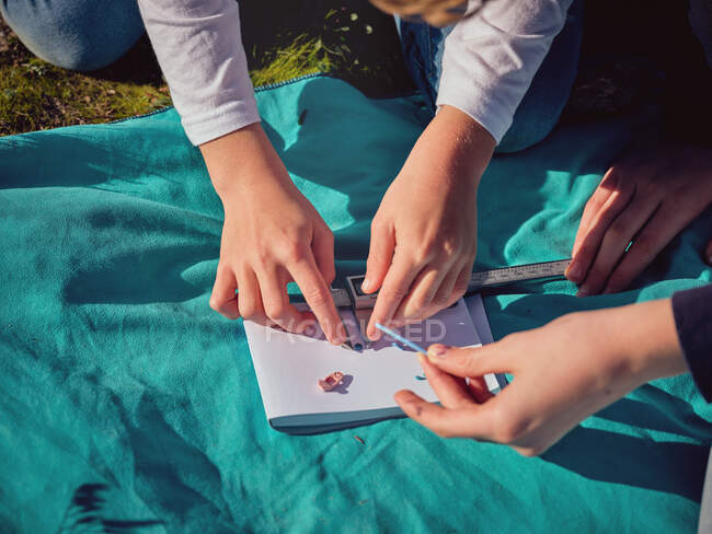 From above crop hands of persons gauging by vernier caliper little plastic things on paper on blue coverlet placed on ground — Stock Photo