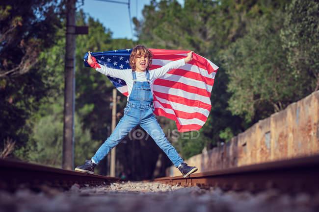 Мальчик с американским флагом во время прыжков по рельсам в сельской местности — стоковое фото