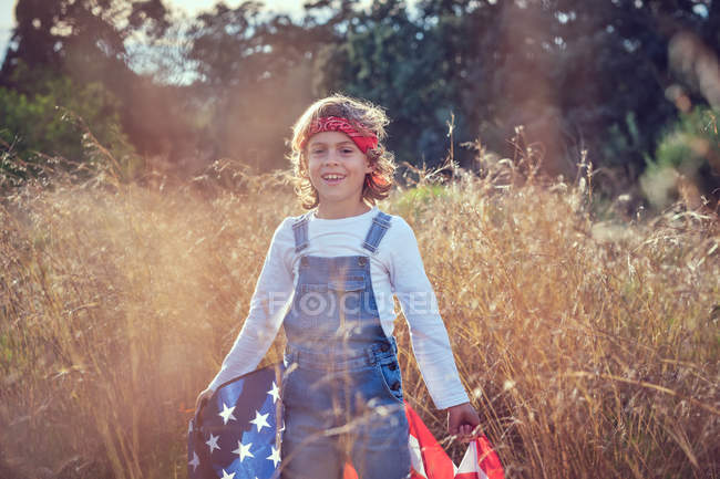 Smiling boy holding American flag in countryside — Stock Photo