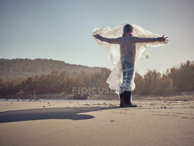 Back view of child with hands to sides entangled in white textile waving by wind on sand shore — Stock Photo