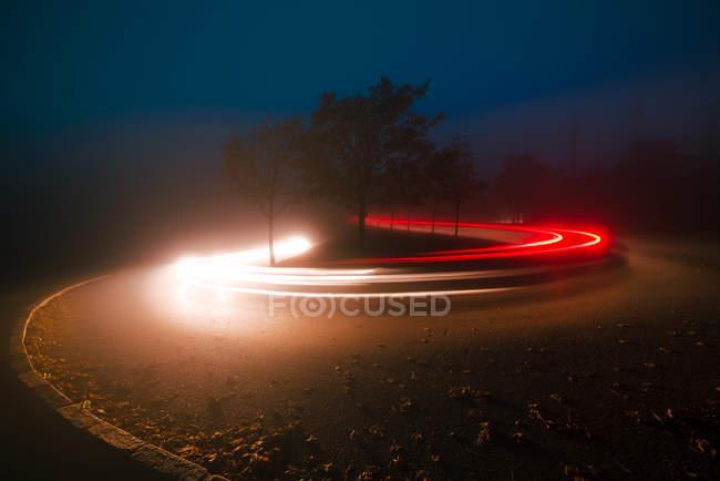 Яскравий слід вогнів між деревами і Мряка у вечір у сільській місцевості — стокове фото