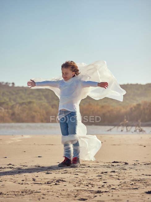 Мальчик, запутавшийся в пластике на берегу реки — стоковое фото