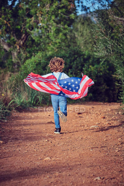Boy holding with American flag on path in countryside — Stock Photo