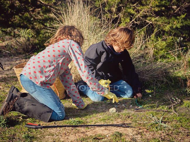 Niños limpiando basura del suelo en el parque cerca de contenedores y recolectores de basura - foto de stock