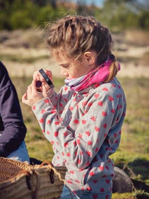 Молода жінка біля хлопчика і дівчинки сидить на землі біля контейнера в парку. — стокове фото