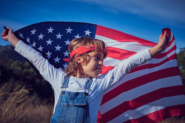 Мальчик, держащий американский флаг и смотрящий в сторону природы — стоковое фото