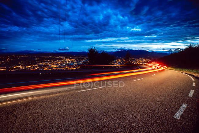 Vista di luci luminose sul percorso in serata in campagna sullo sfondo della città e cielo nuvoloso — Foto stock