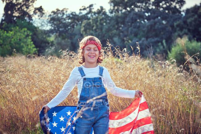 Счастливый мальчик с закрытыми глазами держит американский флаг в сельской местности — стоковое фото