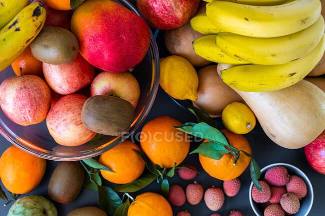 Colección de diferentes frutas tropicales frescas y sabrosas en cuencos y platos en la mesa cerca de la pared - foto de stock