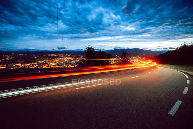 View of bright trail lights on route in evening in countryside on city background and cloudy sky — Stock Photo