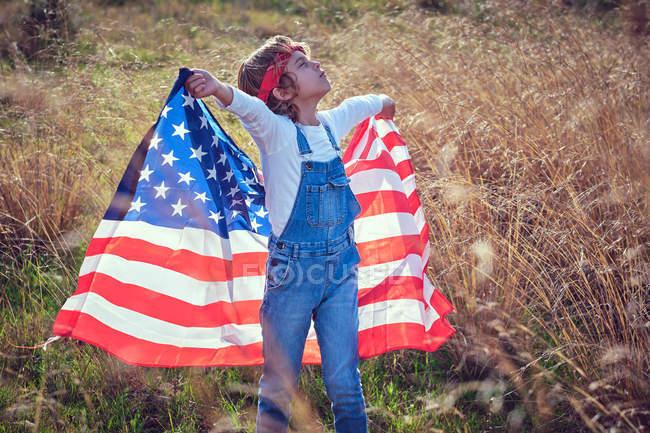 Menino orgulhoso com os olhos fechados segurando bandeira americana no campo — Fotografia de Stock