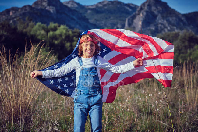 Portrait of boy holding American flag in nature — Stock Photo