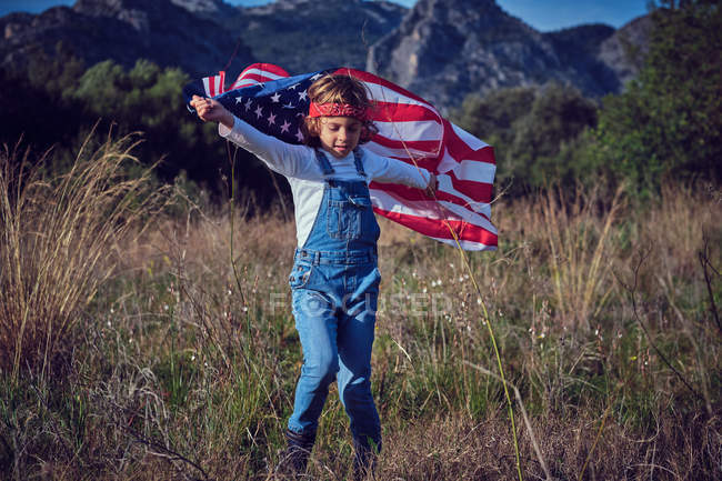 Boy standing with American flag in nature — Stock Photo
