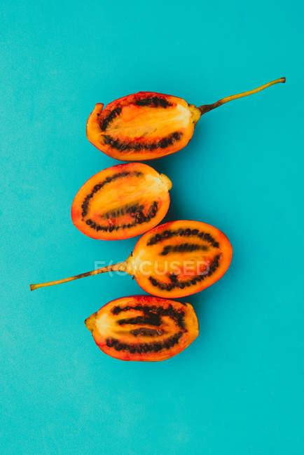 Cuatro mitades de delicioso tamarillo cortado sobre fondo azul brillante - foto de stock