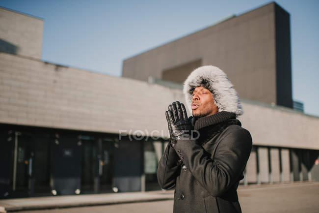 Стильный афроамериканец в меховой шапке стоит напротив современного здания в солнечный день и массирует руки — стоковое фото