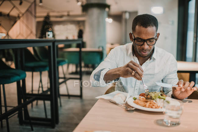 Adult African American male enjoying delicious food while sitting at table in stylish restaurant — Stock Photo