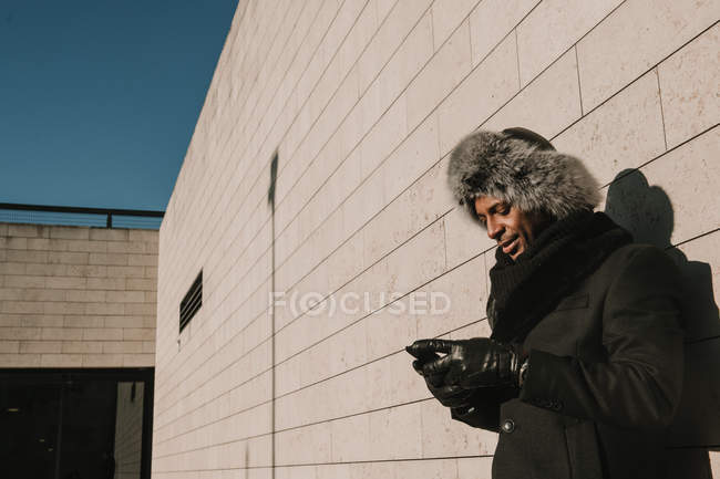 African American male in fur hat leaning on brick wall with mobile phone on sunny day on city street — Stock Photo