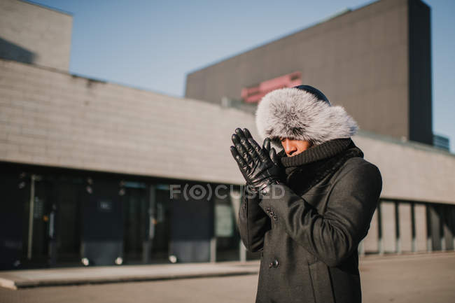 Stylish African American male in fur hat standing against modern building on sunny day and rubbing hands — Stock Photo