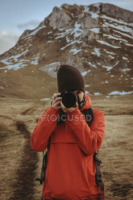 Woman in red jacket using professional photo camera while standing near beautiful snowy mountains in amazing countryside — Stock Photo