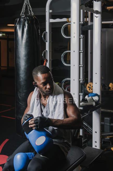 Чернокожий мужчина надевает боксерские перчатки — стоковое фото