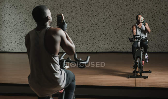 Back view of African American man taking selfie while sitting on exercise bike in front of mirror in modern gym — Photo de stock