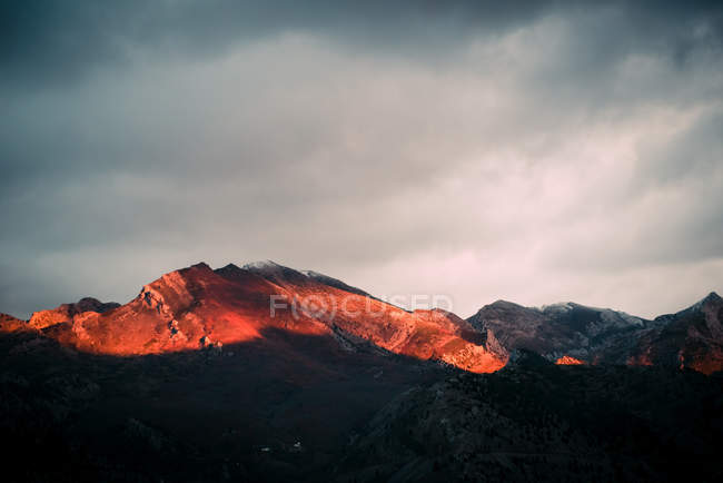 Cloudy sky over mountain ridge at sunset — Stock Photo
