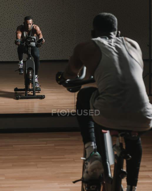 Black guy making selfie on exercise bike in gym — Photo de stock