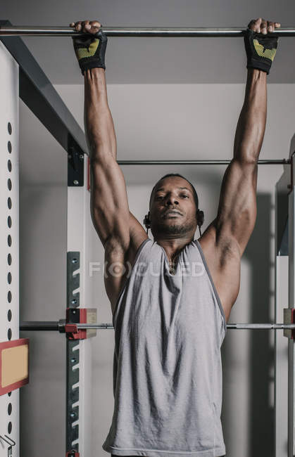 Black muscular guy hanging on bar in gym — стоковое фото