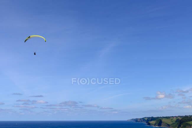 Великолепный вид беспилотника на ярких парапланеристов, летящих против облачного неба над красивой зеленой природой в солнечный день — стоковое фото