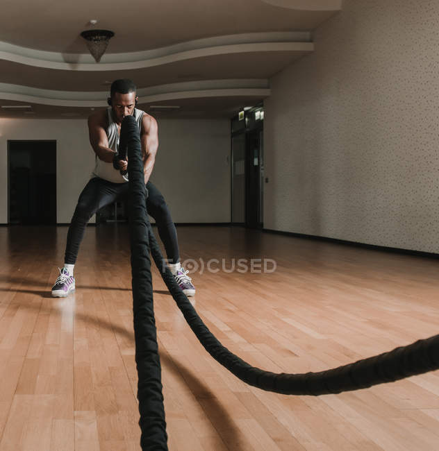 Black guy exercising with ropes in gym — Stock Photo