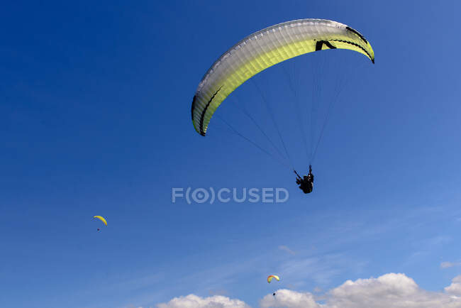 Magnificent drone view of bright paragliders flying against cloudy sky on sunny day — Stock Photo