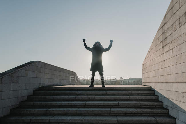 African American guy in warm clothes looking up and gesturing with hands while celebrating victory on top of stairway on sunny day in city — Stock Photo
