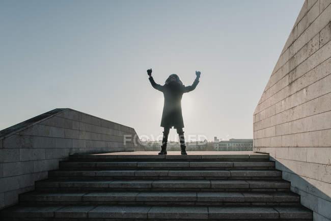 Афроамериканский парень в теплой одежде смотрит вверх и жестикулирует руками, празднуя победу на вершине лестницы в солнечный день в городе — стоковое фото