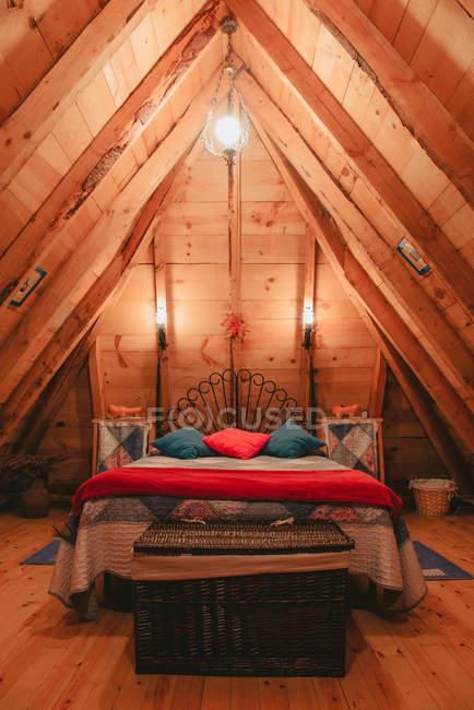 Удобная кровать с теплым одеялом и мягкими подушками под необычными лампами на уютном чердаке лесопилки — стоковое фото