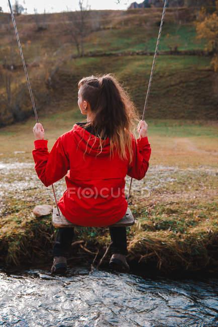 Vue arrière de la jeune femme avec coiffure élégante assise sur la balançoire sur le ruisseau avec de l'eau fraîche et propre dans une nature magnifique — Photo de stock