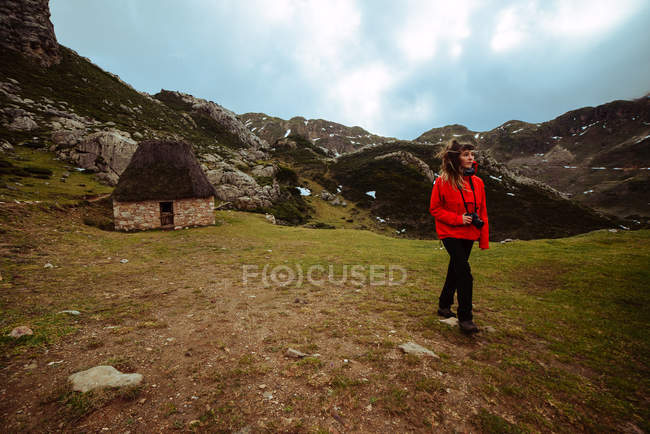 Young woman in red jacket walking and looking at mountainous countryside against cloudy sky — Stock Photo