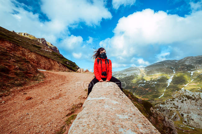 Woman in red jacket and scarf sitting near countryside road on mountain slope on cloudy daytime in amazing nature — стокове фото