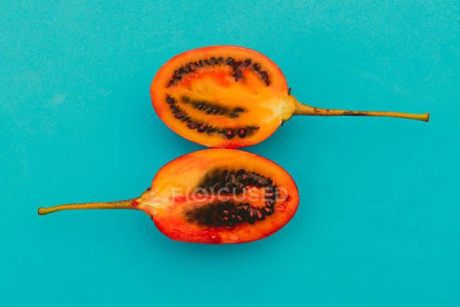Dos mitades de delicioso tamarillo cortado sobre fondo azul brillante - foto de stock