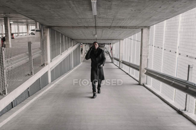 African American man in stylish outfit walking in passage of modern building and having smartphone conversation — Stock Photo