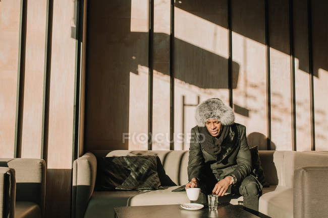 Handsome African American man in warm outfit holding cup of hot beverage and looking away while sitting on comfortable sofa in cafe — Stock Photo