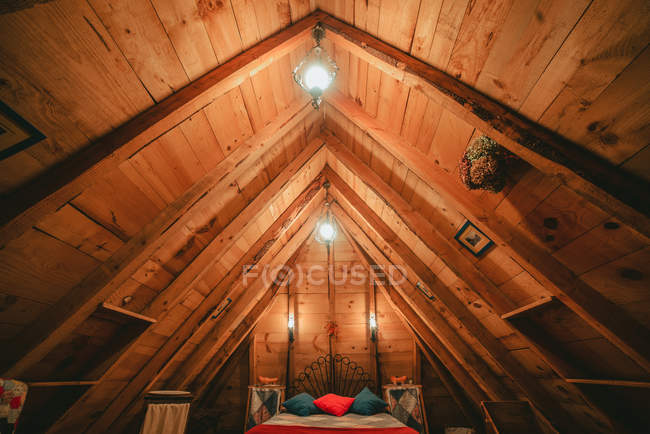 Comfortable bed with warm blanket and soft pillows under unusual lamps in cozy attic of lumber house — Stock Photo