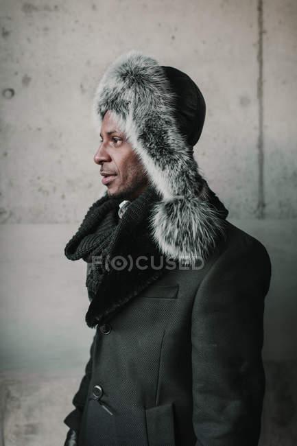 Вид сбоку на красивого афроамериканца в стильной меховой шляпе, стоящего у бетонной стены — стоковое фото