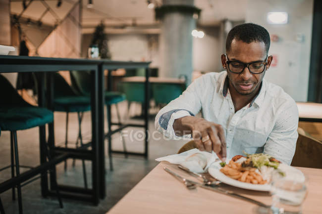Adult African American man enjoying delicious food while sitting at table in stylish restaurant — Stock Photo