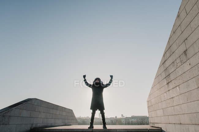 Афроамериканец в теплой одежде смотрит вверх и жестикулирует руками, празднуя победу на вершине лестницы в солнечный день в городе — стоковое фото