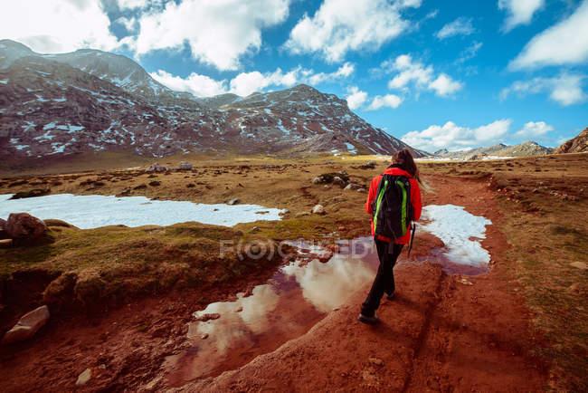 Vue arrière d'une femme avec sac à dos marchant sur l'herbe sèche de la merveilleuse vallée vers la crête de montagne spectaculaire — Photo de stock