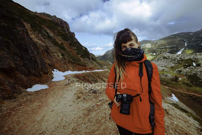 Femme dans la veste rouge avec l'appareil-photo professionnel tout en restant près de belles montagnes enneigées dans la campagne étonnante — Photo de stock