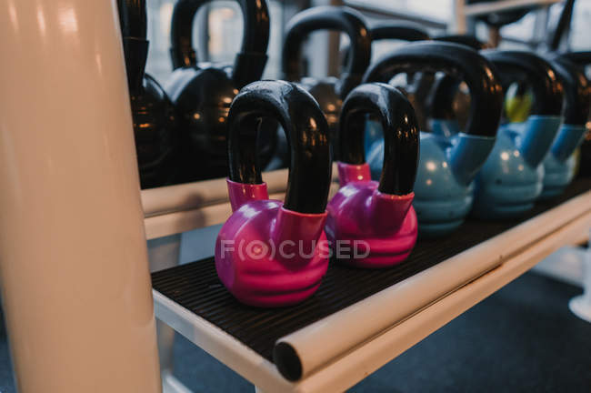 Modern kettle bells of various sizes lying on rack in modern gym — Fotografia de Stock