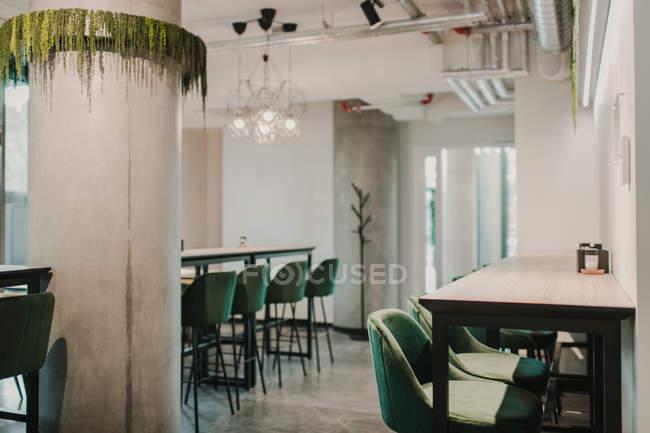 Mesas modernas e cadeiras confortáveis em pé dentro do café acolhedor — Fotografia de Stock