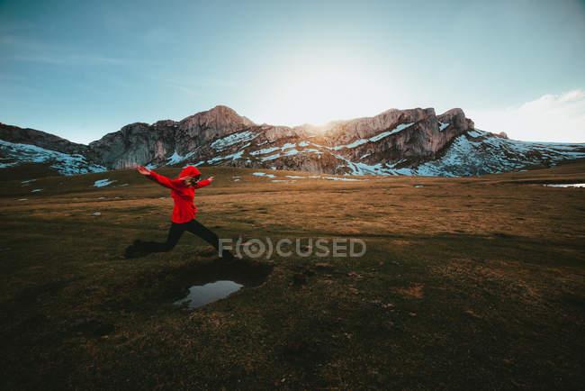 Vue latérale d'une femme sautant sur l'herbe sèche d'une vallée magnifique vers une crête de montagne spectaculaire — Photo de stock