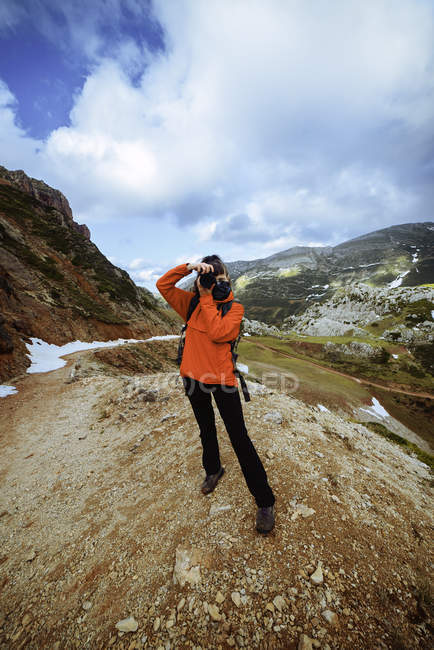Femme méconnaissable avec l'appareil-photo restant contre les montagnes majestueuses et le ciel nuageux dans la campagne merveilleuse — Photo de stock